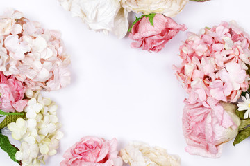 Frame made of pink and beige roses, hydrangea, green leaves, branches on white background. Flat lay, top view. Wedding's background. Valentines day background with copy space.