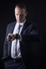 Businessman standing on Black Background, Man wacthing time on black background. People with busy for business concept.