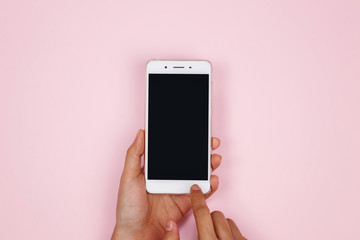 Woman hands holding smartphone on pink background with copy space. Flat lay. Top view. Wall mural