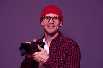 Positive hipster man in stylish clothes photographer holds camera and posing on background in violet color tone