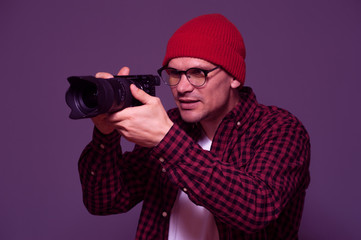 Positive hipster man in stylish clothes photographer holds camera and takes photo on background in violet color tone