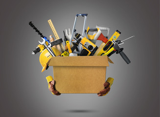 Construction tools and helmet in cardboard box