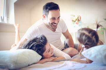 Happy family playing on a bed with little girl.
