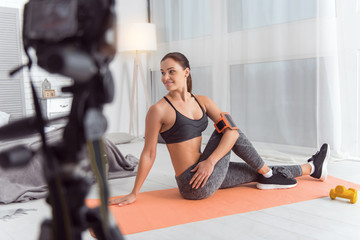 Doing good exercises. Nice content athletic dark-haired young woman smiling and doing exercises for her back while sitting on the carpet and making a video for her blog