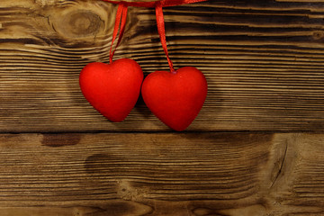 Two red hearts hanging over wooden background