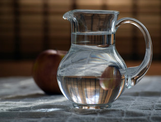 Glass jug of water and an Apple