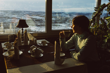 the woman is sitting in a cafe and drinking tea on the background of the mountains