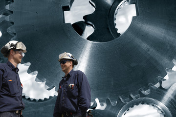 Wall Mural - industry workers with giant titanium gear machinery, steel mill works