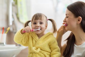 Beautiful mother and kid brushing teeth in bathroom