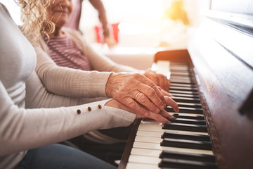 A girl with grandmother playing the piano.
