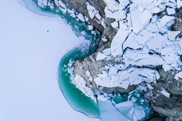 Thaw lake, blocks of ice and turquoise water. View from above with drone