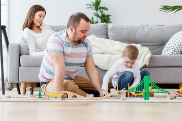 Photo of father playing with son in toys sitting on floor, sitting next to pregnant mother