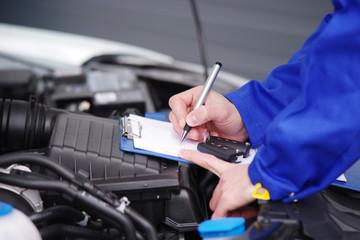 Mechaniker bei der Durchsicht eines Autos, TÜV-Untersuchung