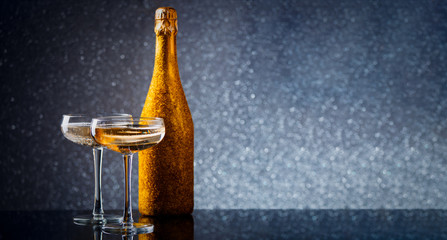 Photo of bottle of wine in gold wrapper with two wine glasses on gray background