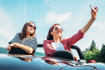 Two female freinds take a selfie photo in cabriolet car during their summer voyage
