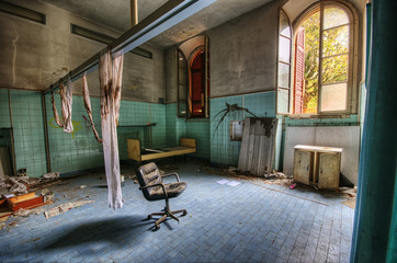 abandoned interior of a former hospital with beds, chairs and blankets covered in blood
