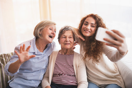 A teenage girl, mother and grandmother with smartphone at home.