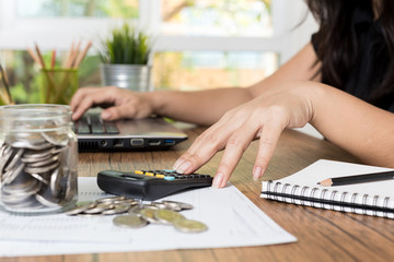 Saving money and finances concept, Close up hand woman hand put coins in jug glass with Calculate with a calculator.