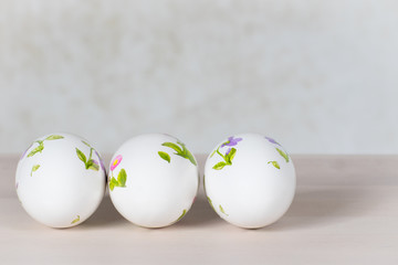 Three white eggs with painted flowers, simple design background