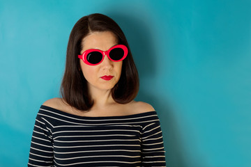 Woman in blue striped top and red sunglasses on a blue background.