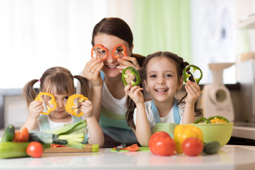 Happy family mother and kids having fun with food vegetables at kitchen holds pepper before their eyes like in glasses