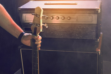 The bass guitarist connects the bass guitar to the amplifier on the stage.