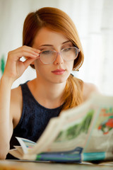 Young girl reading newspaper in eyeglasses