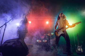 Rock band performs on stage. Guitarist, bass guitar and drums.