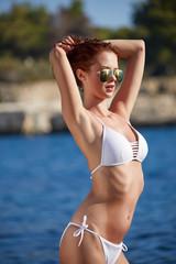 Young adult slim woman in 20s posing on rocks on adriatic sea coast wearing bikini. Toned image.