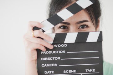 Young Asian woman playing clapperboard with positive emotion
