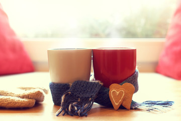 warming drinks for joint pastime/ white and red mug wrapped in a blue scarf and two cookies in the form of hearts in the background of the window