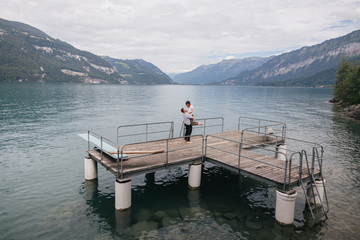 happy young couple on wooden pier in mountain lake, Bern, Switzerland