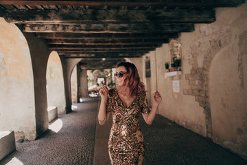 attractive happy girl in glamorous dress walking in old Verona city