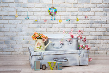 The word LOVE against a white brick wall with vintage suitcases, roses in a metal garden watering can. Studio photo.