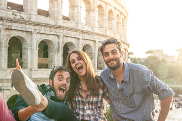 Three young friends tourists in front of colosseum in rome taking funny selfie pictures with smartphone camera. Sunset with lens flare.