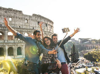 Three happy young friends tourists with bikes and backpacks at Colosseum in Rome taking pictures with smartphone and selfie stick having fun. Ground shot with lens flare.