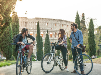 Three young friends tourists with bikes in colle oppio park in front of colosseum on road with trees at sunset having fun talking laughing in Rome lens flare