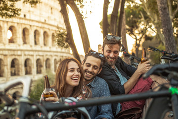 Three young friends tourists with bikes sitting on bench in front of colosseum under tree at sunset drinking beers having fun in Rome