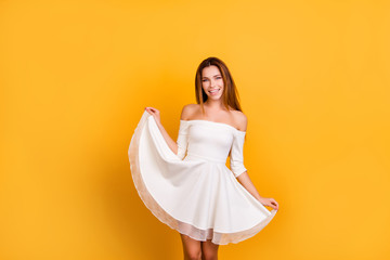 Sensual, romantic girl with naked shoulders holding for the bottom of the skirt, showing her dress, looking at camera standing over yellow background Wall mural