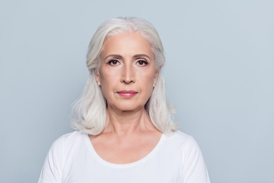 Portrait  of nice, charming, aged, concentrated, woman with serious expression, standing over gray background