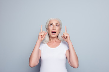 Portrait of perfect, nice, old, impressed woman in t-shirt demonstrate, looking, pointing with two forefingers up to copy space, with open mouth, standing over gray background