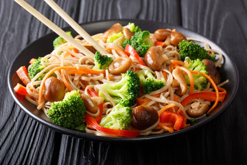 Stir Fry soba with shiitake, broccoli, carrots, peppers close-up on a plate on the table. horizontal