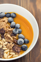 puree of mango with granola, chia and berries in white bowl