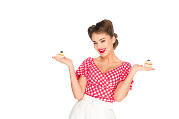 portrait of beautiful woman in pin up clothing with cupcakes isolated on white