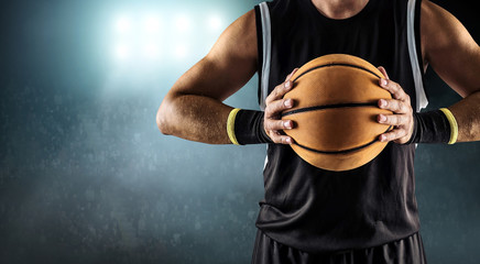 Basketball ball in a male hands, player in black with orange spo
