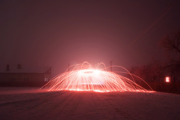 Bright crimson sparks in fog, steel wool photography,