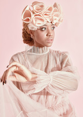 Soft fashion portrait of pretty and serious black woman with light hair and green eyes wearing powder pink tulle dress and big frill hairband and posing with dress in hand.
