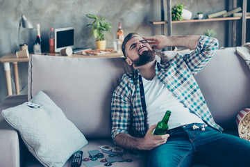 Handsome, stylish man suffering from headache after night party in the morning, holding bottle of beer in hand, sitting on sofa in living room