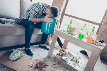 I hate morning after party! Sick tired feeling bad bearded guy with stylish hairdo guy is holding a blue bucket and vomiting, sitting on a couch