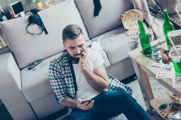 It wasn't I last night! Sad upset troubled nervous bearded gut wearing casual checkered shirt and jeans is sitting on the carpet and watching shameful videos on his smartphone